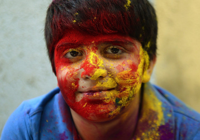A physically challenged Indian child, smeared with gulal-coloured powder, smiles at the camera during Holi celebrations at the Society for the Edcuation of the Crippled school in Mumbai on March 4, 2015.   'Holi', the festival of colours, is a riotous celebration of the coming of spring and falls on the day after full moon annually in March.  Revellers spray coloured powder and water on each other with great gusto, whilst adults extend the hand of peace.  AFP PHOTO / PUNIT PARANJPE        (Photo credit should read PUNIT PARANJPE/AFP/Getty Images)