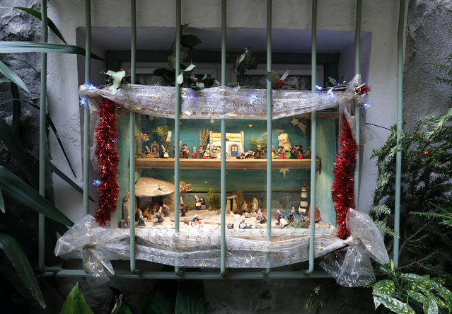 A Nativity scene is seen at a window in the medieval mountain village of Luceram as part of Christmas holiday season, France, December 15, 2016. (Photo by Eric Gaillard/Reuters)