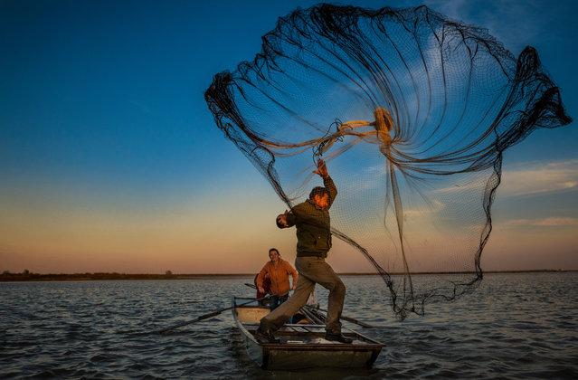 A fisherman throws a net for catching fish with his wife in Yanhu fisherman village near Yangzhou, Jiangsu province, China, 18 October 2018. (Photo by Aleksandar Plavevski/EPA/EFE)