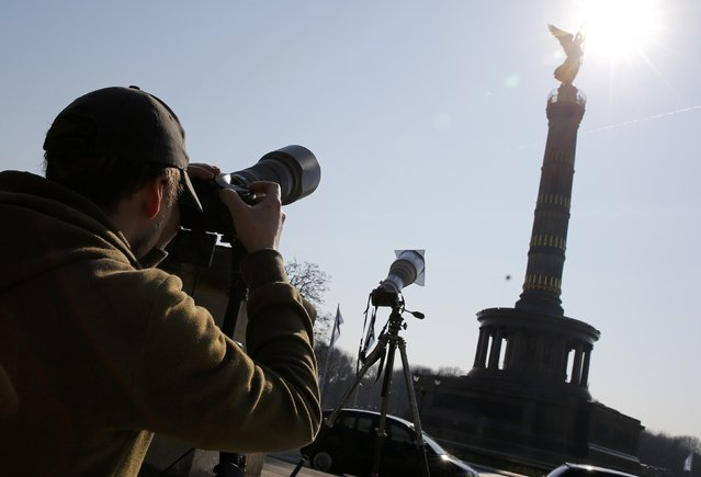 """A man photographs the partial solar eclipse beside the """"Golden Victoria"""" statue on top of the Victory Column (Siegessaule) in Berlin March 20, 2015. (Photo by Fabrizio Bensch/Reuters)"""