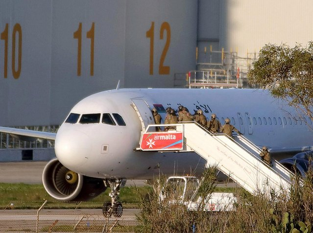 Special forces enter the hijacked Afriqiyah Airways airplane at the Malta International Airport in Luqa, Malta, 23 December 2016. The plane of Libyan carrier Afriqiyah Airways with 118 people on board landed in Malta after being hijacked and diverted during its internal flight in the North African country. The two hijackers were detained by police after all passengers and crew members were freed. (Photo by Domenic Aquilina/EPA)