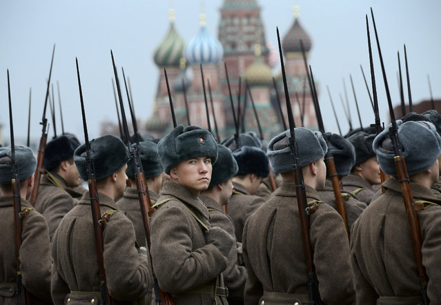 Russian soldiers dressed in Red Army World War II uniforms prepare to parade in Red Square in front of a backdrop of St. Basil Cathedral in Moscow, Russia, Thursday, November 7, 2013. Thousands of Russian soldiers and military cadets marched across Red Square to mark the 72nd anniversary of a historic World War II parade. The show honored the participants of the Nov. 7, 1941 parade who headed directly to the front lines to defend Moscow from the Nazi forces. The parade Thursday involved about 6,000 people, many of them dressed in World War II-era uniforms. (Photo by Alexander Zemlianichenko/AP Photo)