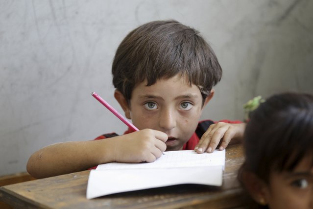 A boy attends a class inside a school in the southern countryside of Idlib, Syria September 20, 2015. (Photo by Khalil Ashawi/Reuters)