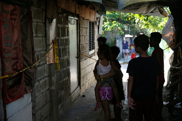 Residents stand outside a house where 7 people were shot dead by suspected vigilantes at a house storing illegal narcotics, police said on Thursday, in Caloocan city, Metro Manila, in the Philippines December 29, 2016. (Photo by Erik De Castro/Reuters)