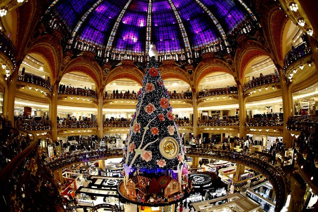 A giant Christmas tree stands in the middle of the Galeries Lafayette department store in Paris. (Photo by Charles Platiau/Reuters)