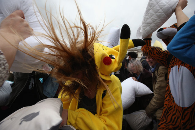 """Revellers take part in a giant pillow fight in Trafalgar Square on """"International Pillow Fight Day"""" on April 4, 2015 in London, England. Pillow fights have been organised in numerous other cities around the world simultaneously. (Photo by Dan Kitwood/Getty Images)"""