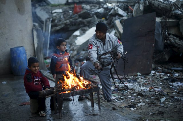 A Palestinian man uses tree branches to stoke a fire to warm himself and his grandsons near the ruins of a house destroyed during 2014 war, on a stormy day in Beit Hanoun in the northern Gaza Strip February 7, 2016. (Photo by Suhaib Salem/Reuters)