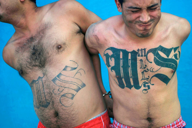 Two members of the Mara Salvatrucha gang are pictured after being detained by Salvadoran army soldiers and policemen during an operation in San Salvador, on January 19, 2019. (Photo by Marvin Recinos/AFP Photo)