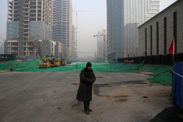 A guard keeps watch at a construction site in Beijing, China, December 31, 2016. (Photo by Thomas Peter/Reuters)