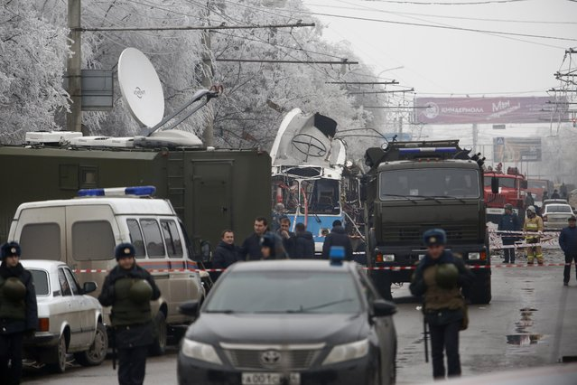 Military vehicles surround a wreckage of a trolleybus, in Volgograd, Russia, Monday, December 30, 2013. A bomb blast tore through a trolleybus in the city of Volgograd on Monday morning, killing at least 10 people a day after a suicide bombing that killed at least 17 at the city's main railway station. Volgograd is about 650 kilometers (400 miles) northeast of Sochi, where the Olympics are to be held. (Photo by Denis Tyrin/AP Photo)