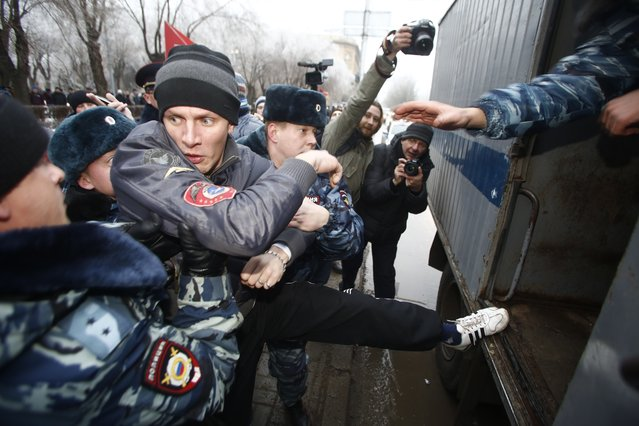 Police officers detain people who gathered for an unsanctioned event in downtown Volgograd, Russia, Monday, December 30, 2013. A bomb blast tore through a trolleybus in the city of Volgograd on Monday morning, killing at least 10 people a day after a suicide bombing that killed at least 17 at the city's main railway station. Volgograd is about 650 kilometers (400 miles) northeast of Sochi, where the Olympics are to be held. (Photo by Denis Tyrin/AP Photo)