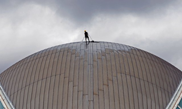 A worker cleans the dome of the Hermisferic of the City of Arts and Sciences in Valencia, Spain, 07 September 2021. The cultural and architectural complex was designed by Santiago Calatrava. (Photo by Juan Carlos Cardenas/EPA/EFE)
