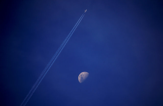 A plane leaves a vapor trail as it flies past the moon above the town of Gunnedah, New South Wales, Australia July 21, 2018. (Photo by David Gray/Reuters)