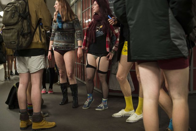 """Participants of the """"No Pants Subway Ride"""" stand on the platform at the Potsdamer Platz station waiting for the U2 Subway line in Berlin on January 12, 2014. (Photo by Odd Andersen/AFP Photo)"""