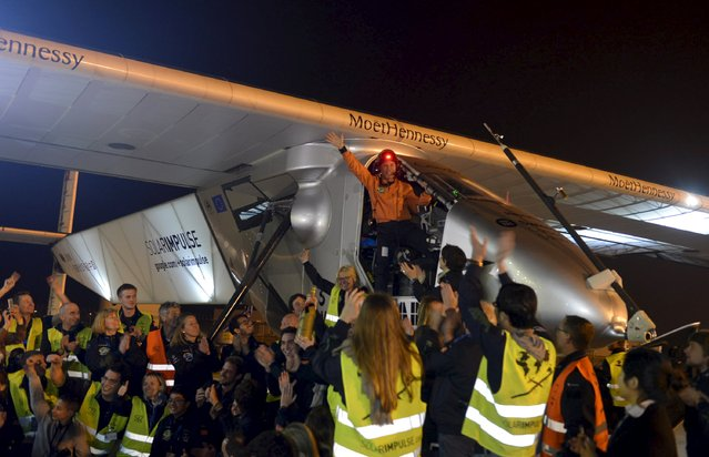 Swiss pilots Bertrand Piccard (top) waves to staff from the cockpit of Solar Impulse 2 plane as they celebrate after the plane landed at Nanjing Lukou International Airport, Jiangsu province April 22, 2015. (Photo by Reuters/Stringer)