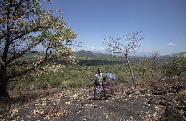 A Sri Lankan man climbs a rock in a forest reserve with a child to access the child's online classes in Bohitiyawa village in Meegahakiwula, Sri Lanka, July 2, 2021. (Photo by Eranga Jayawardena/AP Photo)