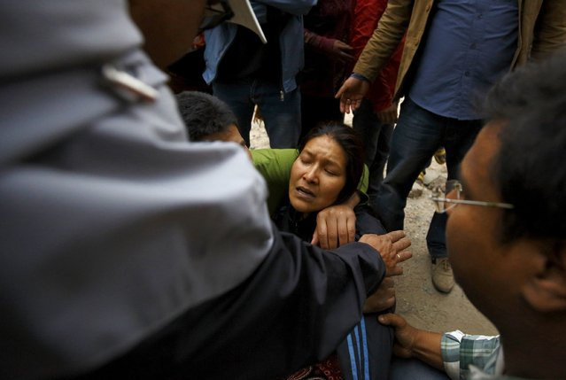 A woman cries as her son was trapped inside a collapsed house after an earthquake hit, in Kathmandu, Nepal April 25, 2015. (Photo by Navesh Chitrakar/Reuters)