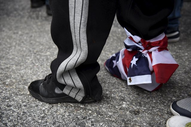 A demonstrator wearing the U.S. flag on a shoe gathers near Camden Yards during a protest against the death in police custody of Freddie Gray in Baltimore April 25, 2015. (Photo by Sait Serkan Gurbuz/Reuters)