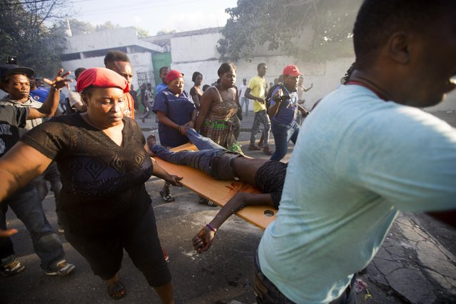 Demonstrators carry the body of a person killed during the violent clashes between the police and demonstrators near the national palace, during a protest to demand the resignation of President Jovenel Moise and demanding to know how Petro Caribe funds have been used by the current and past administrations, in Port-au-Prince, Haiti, Saturday, February 9, 2019. (Photo by Dieu Nalio Chery/AP Photo)