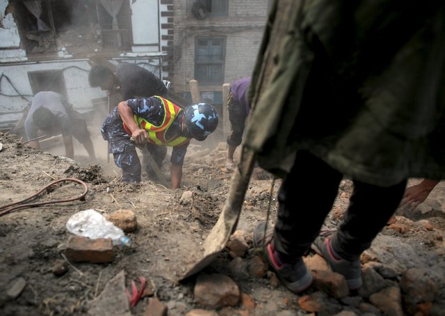 Nepalese police personnel and volunteers clear the rubble while looking for survivors at the compound of a collapsed temple, following Saturday's earthquake, in Kathmandu, Nepal, April 27, 2015. (Photo by Danish Siddiqui/Reuters)