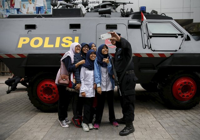 An anti-riot policemen holding a weapon takes a picture with students near an armoured car as he stands guard for a commemorative ceremony for the 1955 Asia-Africa Conference in Bandung, West Java province, April 23, 2015. (Photo by Reuters/Beawiharta)