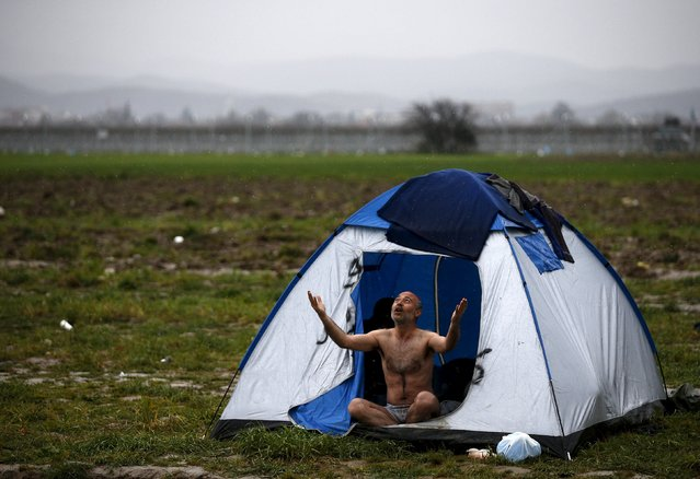 A migrant, who is waiting to cross the Greek-Macedonian border, reacts while being photographed at a makeshift camp near the village of Idomeni, Greece March 9, 2016. (Photo by Stoyan Nenov/Reuters)