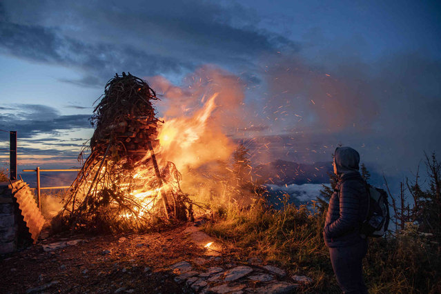 """A traditional high altitude bonfire burns on the occasion of the Swiss National Day on the """"Stanserhorn"""" mountain near Stans, Switzerland, Sunday, August 1, 2021. (Photo by Urs Flueeler/Keystone via AP Photo)"""