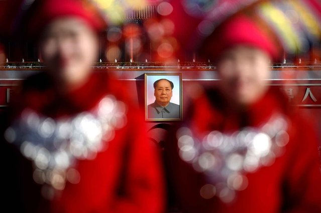 A portrait of late communist leader Mao Zedong is seen behind two hostesses as they pose for a picture at the Tiananmen Square during the 3nd plenary session of the National People's Congress in Beijing on March 13, 2016. China's Communist-controlled parliament opened its annual session on March 5 and is expected to appove a new five-year plan to tackle slowing growth in the world's second-largest economy. (Photo by Wang Zhao/AFP Photo)