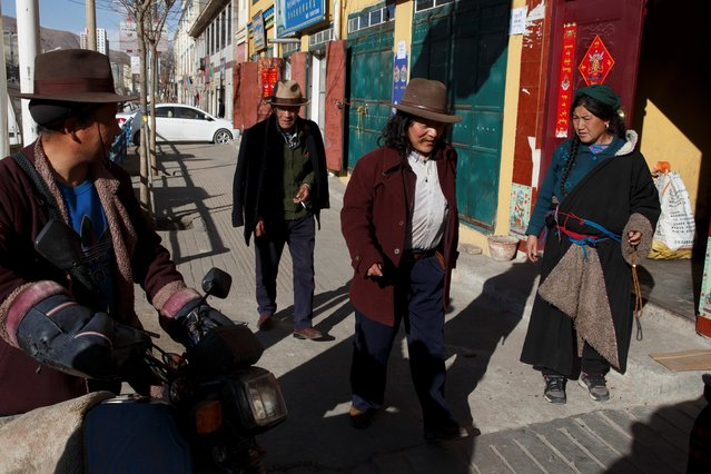 Tibetans walk in a street near Rongwo Monastery in the largely ethnic Tibetan town of Rebkong, Qinghai province, China on March 9, 2019. (Photo by Thomas Peter/Reuters)
