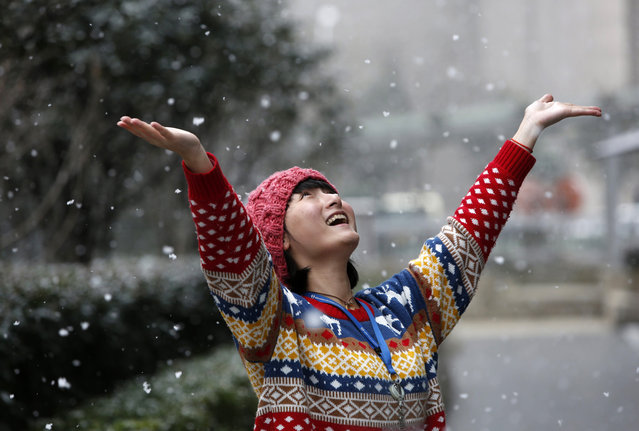 A woman welcomes the snow as she poses for a photograph at Lujiazui financial district of Pudong, in Shanghai on February 10, 2014. (Photo by Aly Song/Reuters)