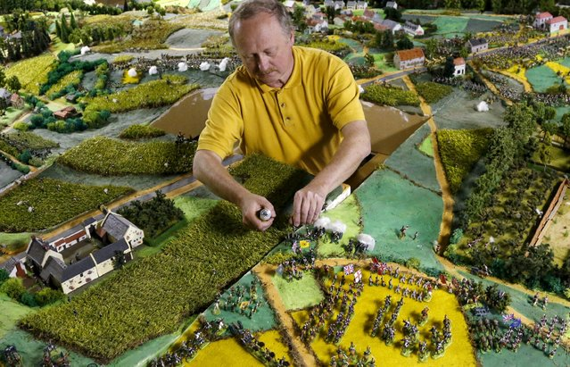 Waterloo enthusiast Willy Smout, 56, adjusts figurines on a 40-square-metre miniature model of the June 18, 1815 Waterloo battlefield, in Diest, Belgium, in this picture taken on April 29, 2015. (Photo by Francois Lenoir/Reuters)
