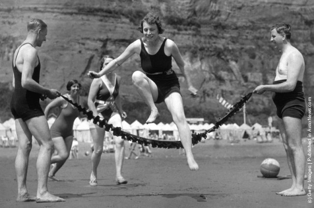 Holiday-makers creating their own enjoyment on the beach, by leaping over strands of seaweed, 1935