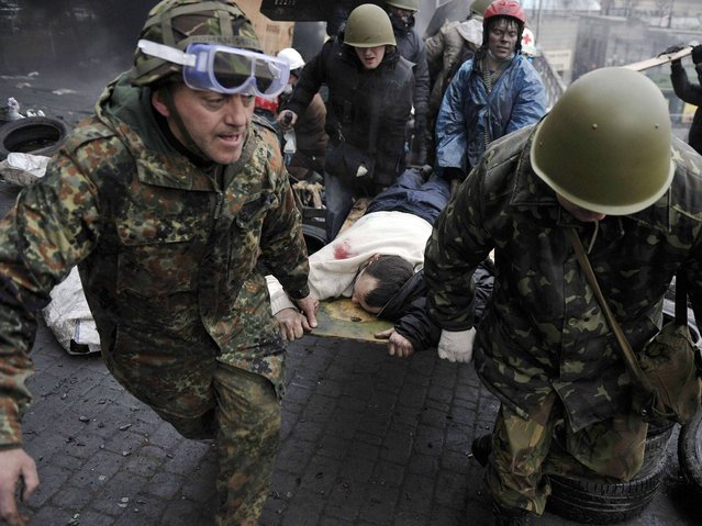 Protesters carry a wounded protester during clashes with police, after gaining new positions near the Independence square in Kiev, on February 20, 2014. (Photo by Louisa Gouliamaki/AFP Photo)