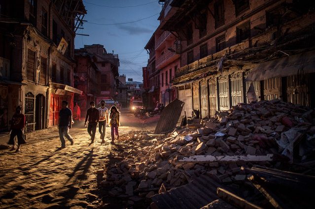 People walk past debris on May 3, 2015 in Bhaktapur, Nepal. A major 7.8 earthquake hit Kathmandu mid-day on Saturday, and was followed by multiple aftershocks that triggered avalanches on Mt. Everest that buried mountain climbers in their base camps. (Photo by David Ramos/Getty Images)