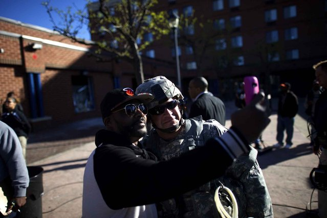 A National Guard soldier poses for a selfie the morning after citywide riots following the funeral of Freddie Gray, on April 28, 2015 in Baltimore, Maryland. (Photo by Mark Makela/AFP Photo)