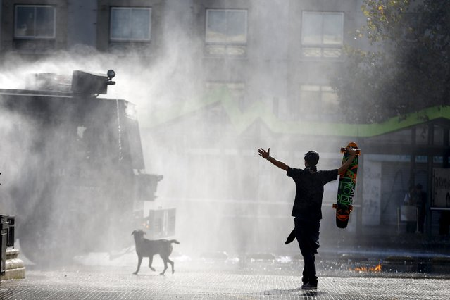 A protester holds up his skateboard in front of a riot police vehicle as they clash during a demonstration to demand changes in the education system at Santiago, May 14, 2015. (Photo by Ivan Alvarado/Reuters)