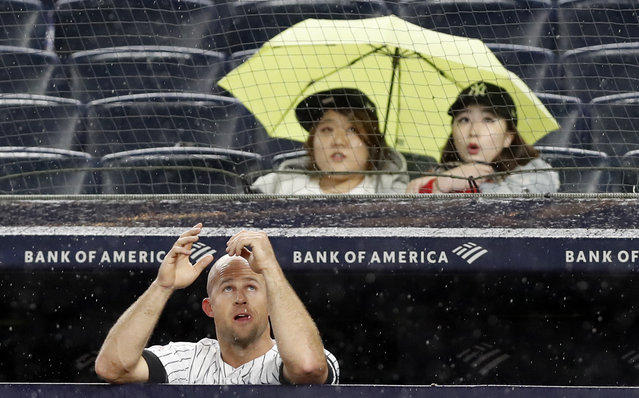 New York Yankees' Brett Gardner looks up at the sky as rain falls during the sixth inning of the team's baseball game against the Seattle Mariners, Tuesday, May 7, 2019, in New York. (Photo by Kathy Willens/AP Photo)