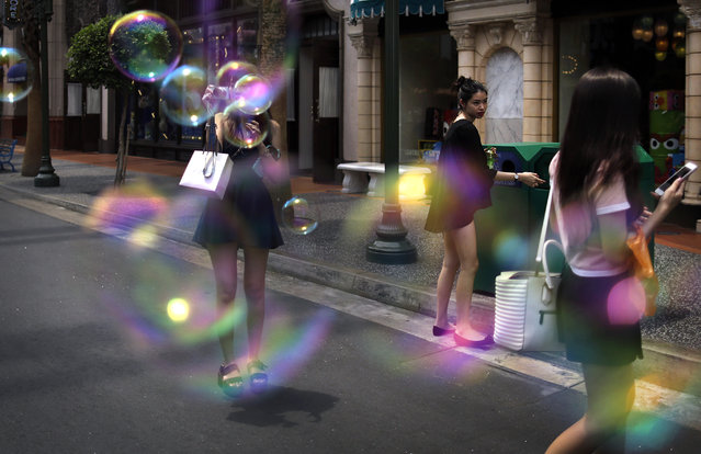 A tourist takes pictures amidst soap bubbles from a mist blowing machine at Universal Studios, a popular tourist destination, Wednesday, April 8, 2015, in Sentosa, Singapore. (Photo by Wong Maye-E/AP Photo)