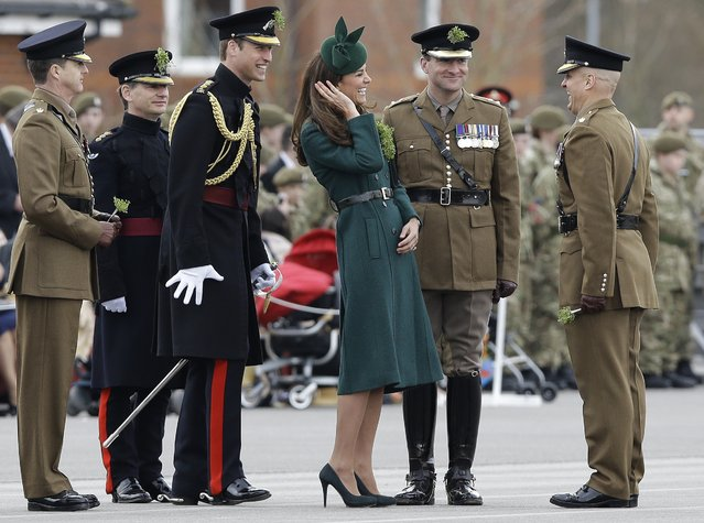 Kate, The Duchess of Cambridge and Prince William smile during a visit to the 1st Battalion Irish Guards at the St. Patrick's Day Parade at Mons Barracks, Aldershot, in England, Monday, March 17, 2014.  The Duke of Cambridge attended the Parade as Colonel of the Regiment. The Duchess of Cambridge presented the traditional sprigs of shamrocks to the Officers and Guardsmen of the Regiment. (Photo by Kirsty Wigglesworth/AP Photo)