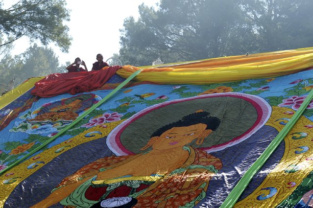 Tibetan monks look on above a giant Thangka, a religious silk embroidery or painting displaying a Buddha portrait, at a prayer ceremony to mark the Buddha's birthday, in Kangding county, Garze Tibetan Autonomous Prefecture, Sichuan province, China, May 25, 2015. Chinese Buddhists celebrate the birthday of Gautama Buddha on Monday, which falls on the eighth day of the fourth month in the Chinese lunar calendar. (Photo by Reuters/Stringer)