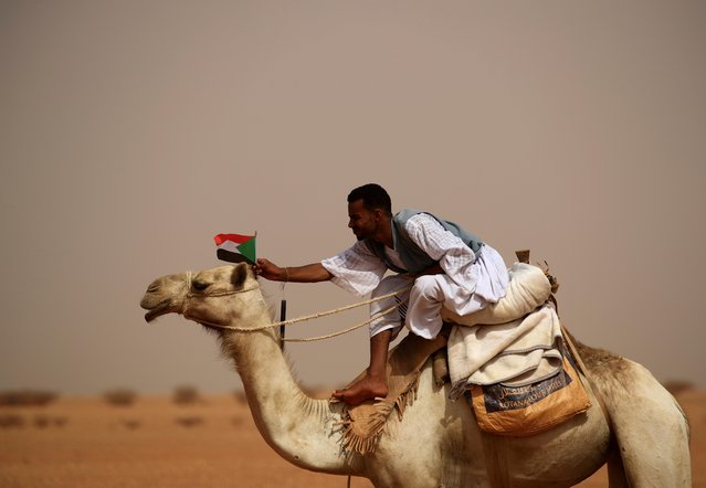A supporter of Lieutenant General Mohamed Hamdan Dagalo, deputy head of the military council and head of paramilitary Rapid Support Forces (RSF), attaches a Sudanese national flag to the head of his camel during a meeting in Aprag village, 60 kilometers away from Khartoum, Sudan, June 22, 2019. (Photo by Umit Bektas/Reuters)