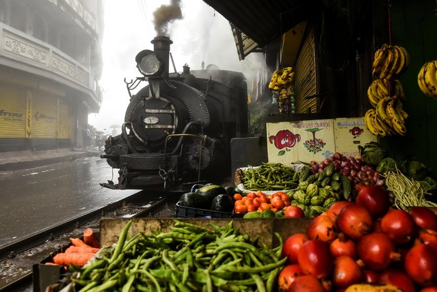 A Darjeeling Himalayan Railway steam train, which runs on a 2 foot gauge railway and is a UNESCO World Heritage Site, passes by a market in Ghum, India, June 27, 2019. (Photo by Ranita Roy/Reuters)
