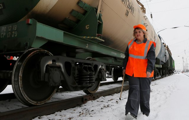 Anastasia Pustovoitova, a senior inspector of railway cars, who is also a model of the SibPlus Models agency and a participant of the Miss Doughnut 2016 beauty competition, inspects a train at the Yenisei railway station of the Trans-Siberian Railway in Krasnoyarsk, Siberia, Russia March 3, 2017. (Photo by Ilya Naymushin/Reuters)
