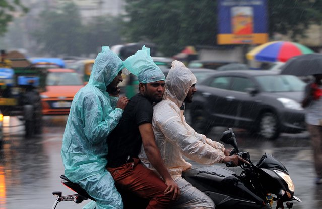 Commuters are seen on road as they move wade through in the monsoon rain in the eastern Indian state Odisha's capital city Bhubaneswar on 3 July 2019. (Photo by NurPhoto via Getty Images/Stringer)