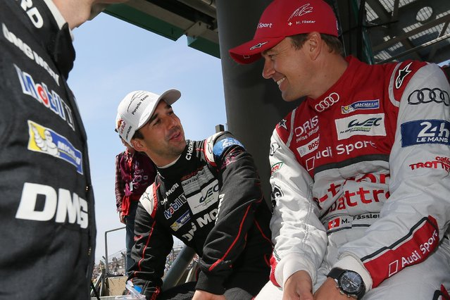 Porsche 919 No18 Swiss driver Neel Jani, left, talks with Audi No7 Swiss driver Marcel Fassler, right, before the start of the 83rd 24-hour Le Mans endurance race, in Le Mans, western France, Saturday, June 13, 2015. (AP Photo/David Vincent)