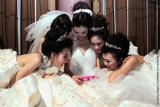 Models looks at an iphone backstage before Tsai Meiyue Wedding Dress S/S 2012 of China Fashion Week