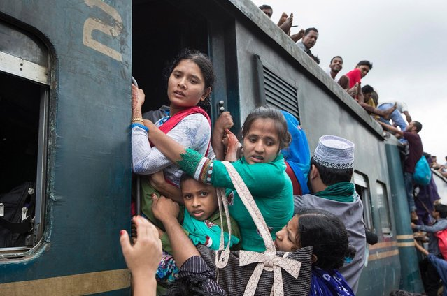 """Documentary film maker Yousuf Tushar said: """"Those who fail to get a place inside the train end up climbing on to the roof or holding on to the sides and fronts of the train so that they can go home"""". (Photo by Yousuf Tushar/Solent News & Photo Agency)"""