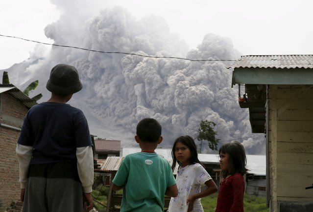 Children gather as they look at ash spewing from Mount Sinabung volcano during an eruption as seen from Kuta Tengah village in Karo Regency, North Sumatra province, Indonesia June 26, 2015. (Photo by Reuters/Beawiharta)