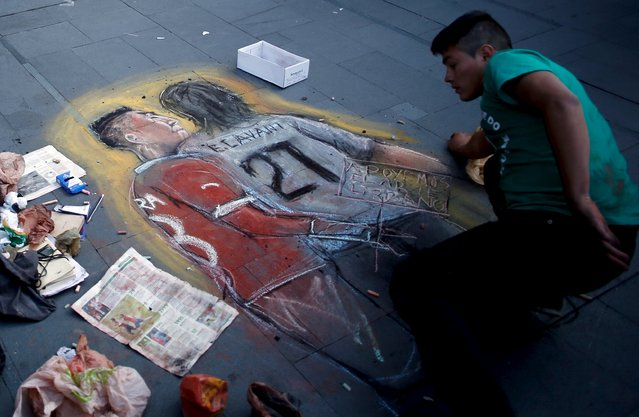 A man draws on the sidewalk a chalk painting of Chile's soccer player Gonzalo Jara and Uruguay's Edinson Cavani, which recreates the moment when Jara provoked Cavani by sticking his finger up his backside, in Santiago, Chile June 28, 2015. The South American Football Confederation (CONMEBOL) suspended Jara for three matches for provoking striker Cavani during their quarter-final match at the Copa America, CONMEBOL officials informed. (Photo by Marcos Brindicci/Reuters)