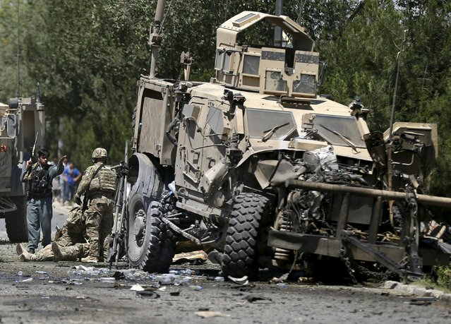 U.S. soldiers attend to a wounded soldier at the site of a suicide bomb attack in Kabul, Afghanistan June 30, 2015. (Photo by Mohammad Ismail/Reuters)